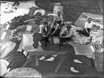 19_Pablo_Picasso_and_scene_painters_sitting_on_the_front_cloth_for_Parade_(Ballets_Russes)_at_the_Theatre_du_Chatelet,_Paris,_1917,_Lachmann_photographer